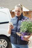 Woman Running Mobile Gardening Business Using Mobile Phone. Woman Running Mobile Gardening Business Uses Mobile Phone Stock Photos