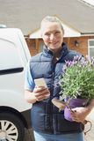 Woman Running Mobile Gardening Business Using Mobile Phone. Woman Running Mobile Gardening Business Uses Mobile Phone Royalty Free Stock Image