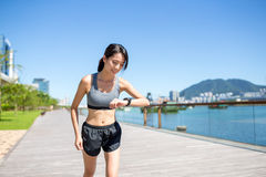 Woman running at morning and checking the record on smart watch Stock Photos