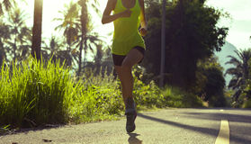Woman running on morning tropical forest trail Stock Photo