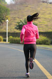 Woman running at mountain driveway Royalty Free Stock Images