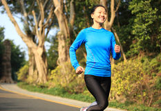 Woman running at mountain driveway Stock Photos