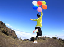 Woman running on mountain peak with colorful balloons Stock Photography
