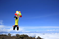 Woman running on mountain peak with colorful balloons Stock Photos