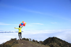 Woman running on mountain peak with colorful balloons Royalty Free Stock Images