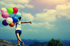 Woman running on mountain peak rock with colored balloons Stock Images