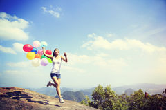 Woman running on mountain peak rock with colored balloons Royalty Free Stock Photography