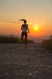 Woman running on a mountain road at summer sunset Stock Image