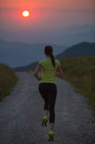 Woman running on a mountain road at summer sunset Royalty Free Stock Photo