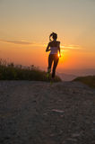 Woman running on a mountain road at summer sunset Royalty Free Stock Images