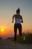 Woman running on a mountain road at summer sunset Royalty Free Stock Photography
