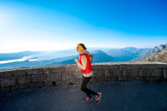 Woman running on the mountain road Stock Photography