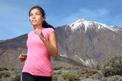 Woman running on mountain trail royalty free stock image
