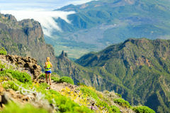 Woman running in mountains on sunny summer day Royalty Free Stock Images
