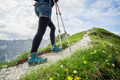 Woman running on narrow mountain trail with hiking poles. royalty free stock photography