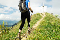 Woman running on narrow mountain trail with hiking poles. royalty free stock photo