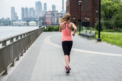 Woman running in New York City Park wearing sport clothes. Royalty Free Stock Photo