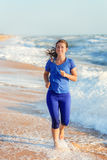 Woman running by the ocean or sea beach Royalty Free Stock Photography