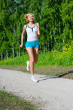Woman running outdoor in a park. An active beautiful caucasian woman running outdoor in a park Stock Photography