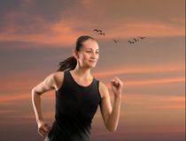 Woman running outdoors against beautiful sky Stock Photos