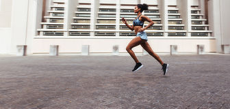 Woman running outdoors. Woman athlete running outdoors in the morning. Woman in running outfit sprinting in the street Royalty Free Stock Photos