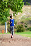 Woman running outdoors on path Stock Images