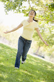 Woman running outdoors smiling Royalty Free Stock Images