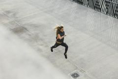Woman running outdoors in the urban city, top view. Of fitness girl running Royalty Free Stock Images