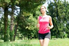 Woman running outdoors Royalty Free Stock Photos