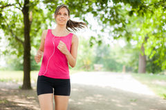 Woman running outdoors Royalty Free Stock Image