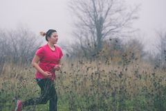 Woman Running Outdoors. Young Woman Running Outdoors in the Nature Royalty Free Stock Photo