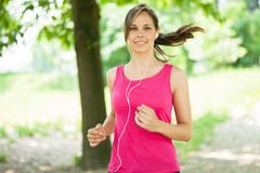 Woman running outdoors Stock Images