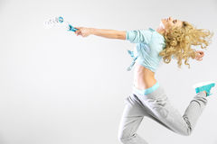 Woman running with a paint roller Stock Image