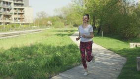 Woman running in park in the morning. Young attractive female in sportswear smiling and running in park in the morning stock video footage