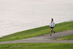 Woman running in park by the sea Royalty Free Stock Photography