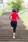 Woman running on park stairs Stock Photo