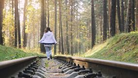 Woman running on railroad in deep pines forest during autumn in slowmotion. 1920x1080 stock video