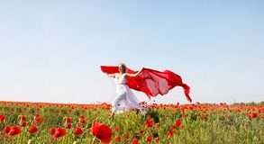 Woman running with red scarf in poppy field Royalty Free Stock Image
