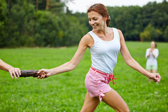 Woman running relay race in a park Stock Photos