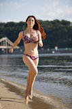 Woman running by the river beach. At sunset Royalty Free Stock Photo