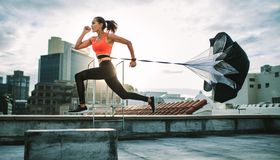 Woman running on rooftop with a resistance parachute. Female athlete training on terrace of a building with a parachute tied behind her. Fitness woman running stock photography