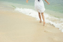 Woman running on the sandy beach - Selective focus Stock Images