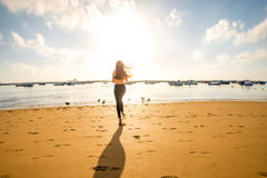 Woman running on the sandy beach. Young woman in black sport clothes running on the sandy beach with seagulls and fishing boats on the background. General plan Royalty Free Stock Images