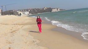 Woman running on sea beach stock video