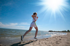Woman running in sea coast. Beautiful young sport woman running in sea coast on sunny summer day Royalty Free Stock Photography