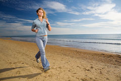 Woman running at sea shore Stock Photo