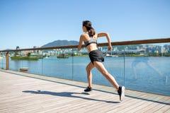 Woman running at seaside boardwalk Stock Photos
