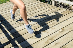 Woman Running Shadow. Legs and shadow of a young woman running outdoors Stock Image