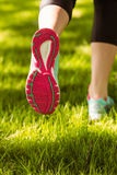 Woman in running shoes jogging on grass. In the park royalty free stock photos