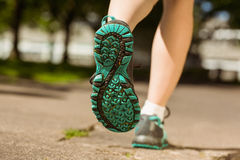Woman in running shoes jogging on path Royalty Free Stock Image